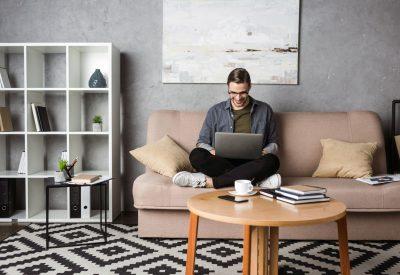 homem sentando num sofá estudando com um notebook no colo
